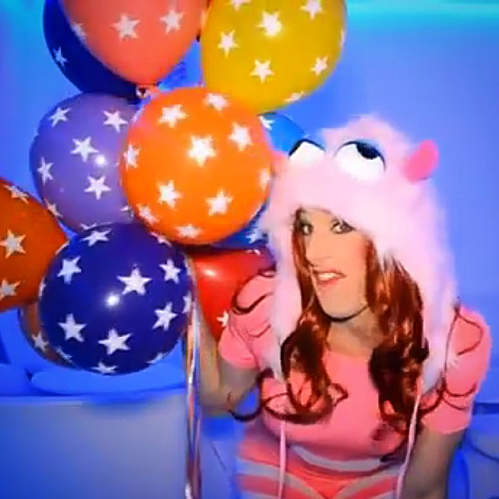 Image shows Declan Buckley as Shirley Temple Bar, who is holding multi-coloured balloons and wearing a goofy furry hat which looks like a monster's head.